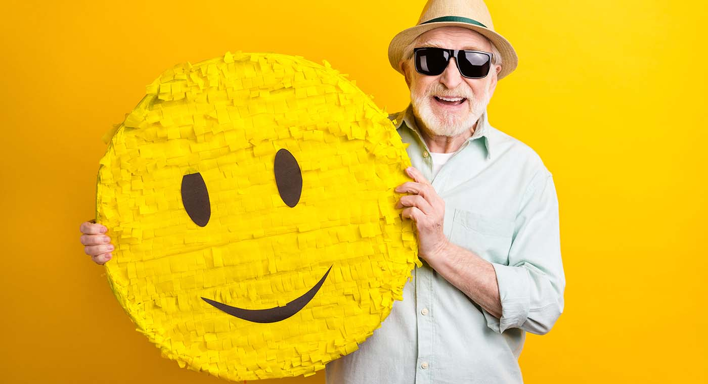 senior man wearing hat and sunglasses holding up a yellow smile face pinata in front of yellow background