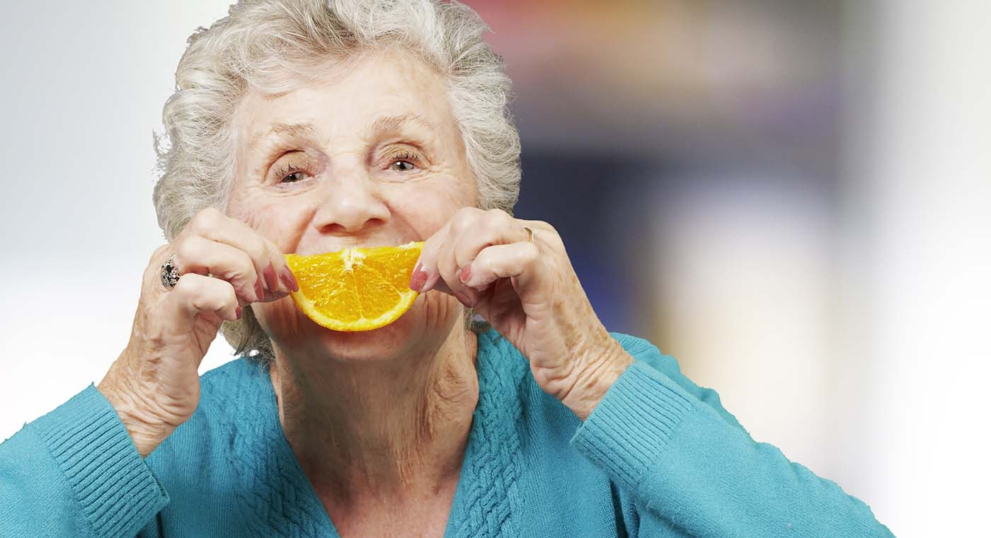 senior woman in blue holding up an orange slice to her face