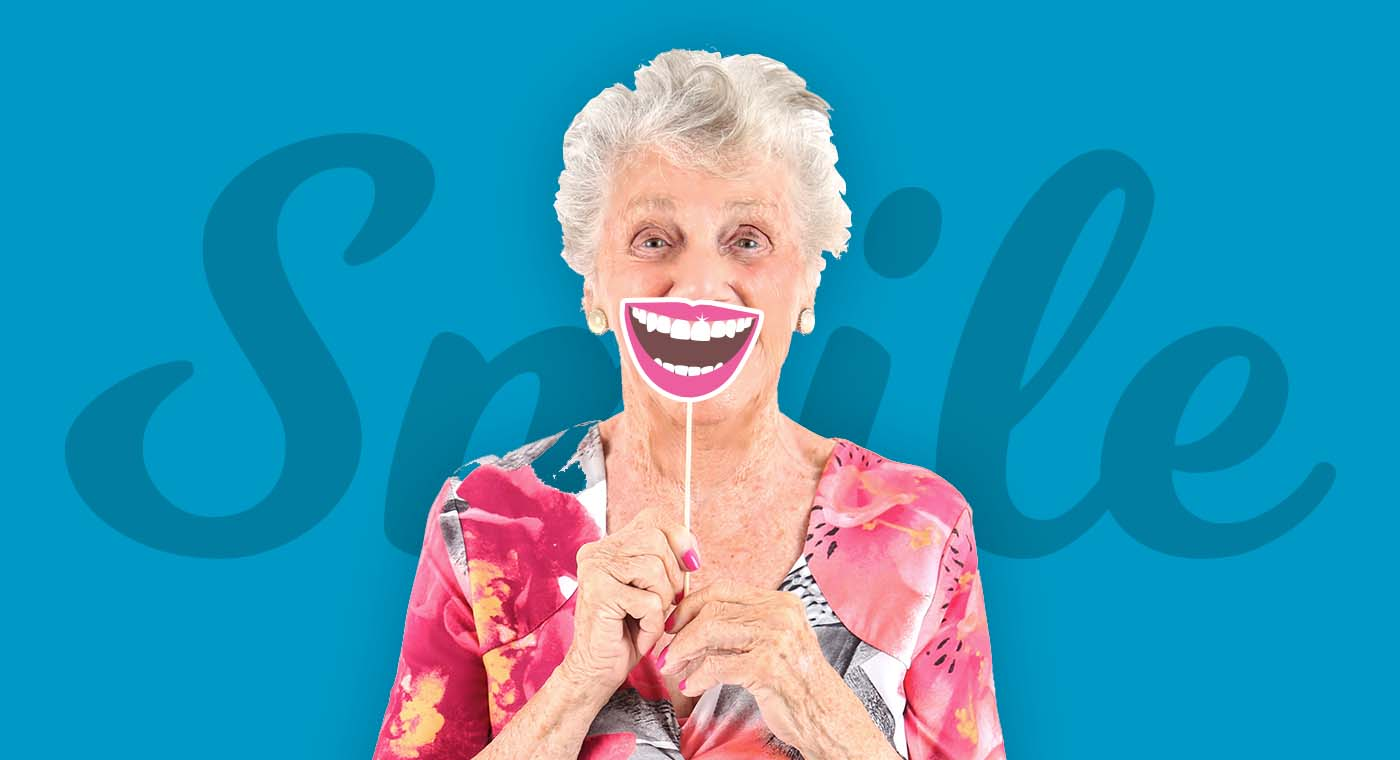 senior woman in floral shirt holding up a smile prop