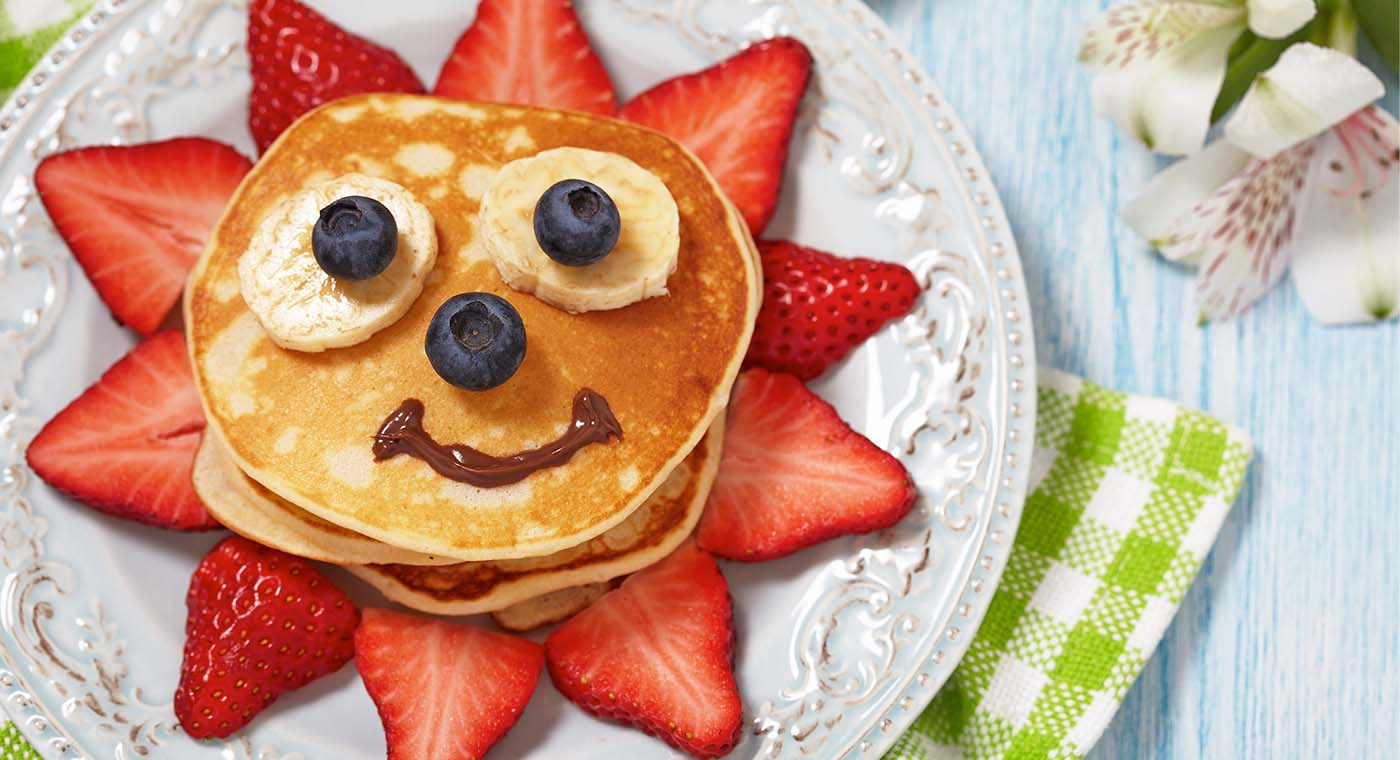 pancake breakfast with strawberries and a face made from blueberries, bananas and maple syrup