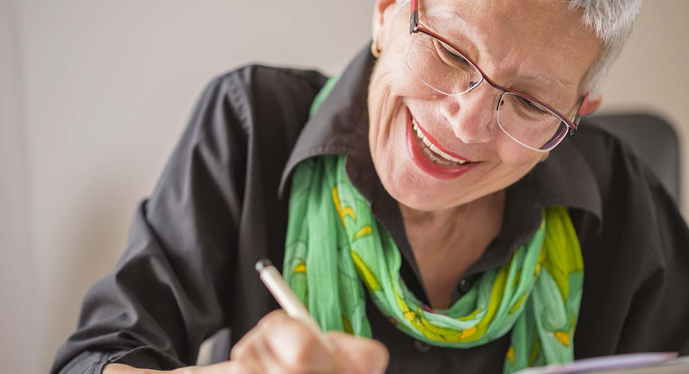 senior woman wearing glasses smiling while writing in book