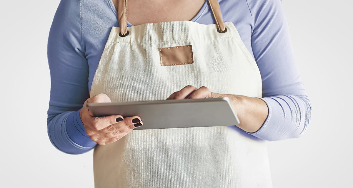Woman with blue shirt in apron working on a tablet with white background