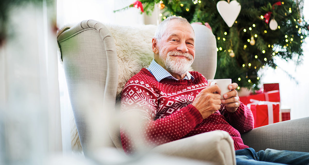 Older man in red christmas sweater, smiling and sitting on chair drinking eggnog at Christmas.