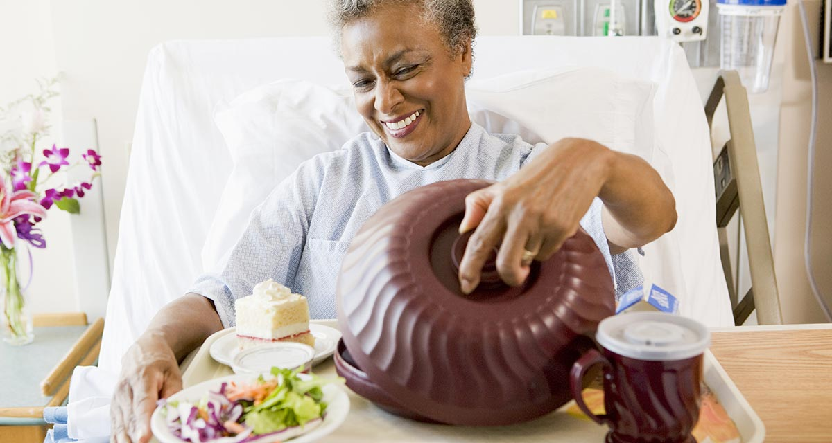 senior-woman-sitting-hospital-bed-tray